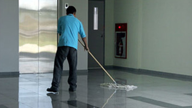 janitor cleaning commercial building floor