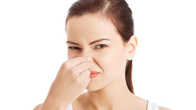 woman holding her nose shut
